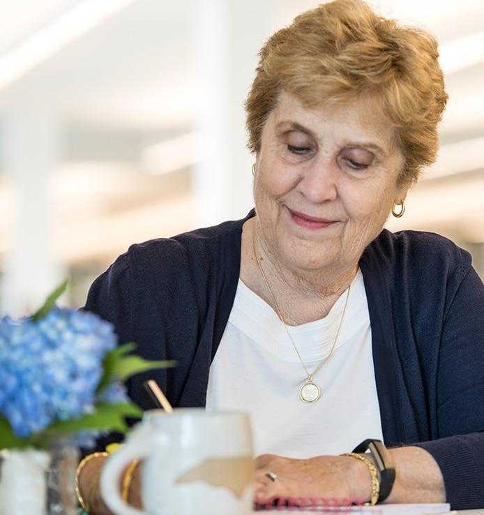 Katherine P. Stillerman writing at her desk.