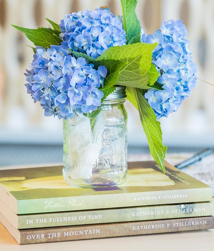 Stack of Katherine P. Stillerman's historical novels with flowers.